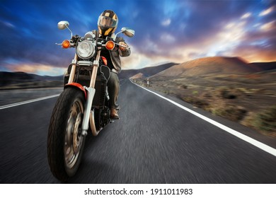 a biker on a motorcycle rides on an asphalt road in the mountains
