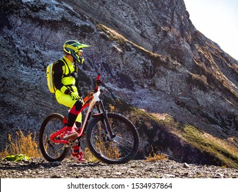 Biker on mountain bike for downhill racing at rock background