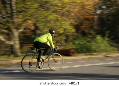 biker on the road speeding past forest in fall colors