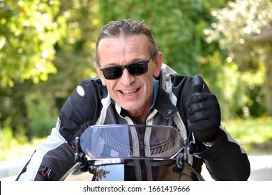 Biker portrait wearing sunglasses and jacket.