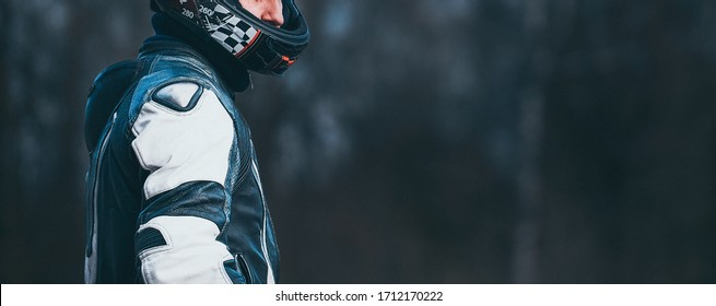Biker in protective suit with a helmet.