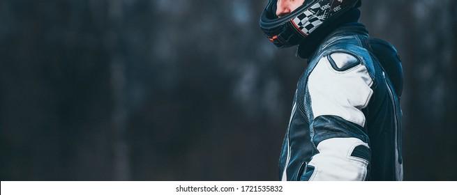 Biker in protective suit with a helmet.