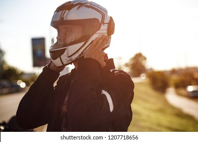 A biker put on his helmet. White helmet on a motorcyclist's head. Reflection of a road in the helmet.