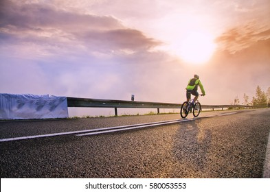 Biker ride down hill on the road in vivid colors of sunset