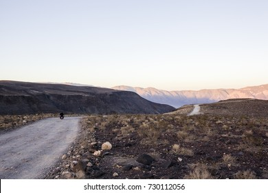 Biker rides off into the sunset in death valley