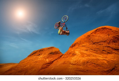 Biker rides on road in the high mountains of sand dunes . Background blue sky with clouds