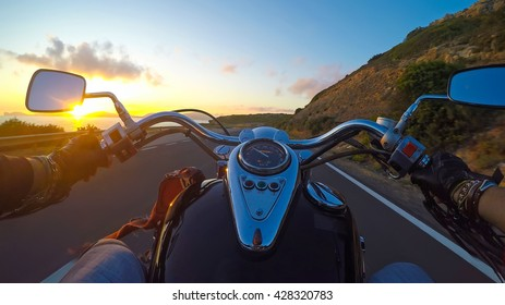 biker riding a classic motorcycle at sunset
