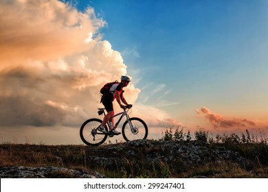 Biker riding on bicycle in mountains on sunset