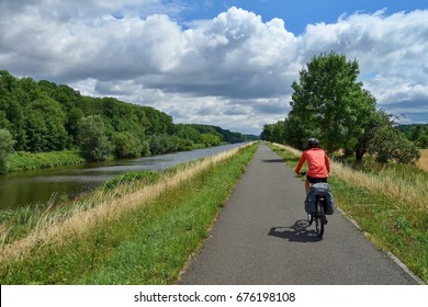 Biker riding on a bicycle path alongside the Morava River in the Czech Republic. Moravian bicycle path number 47. JULY 2017