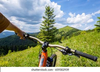 Biker is riding uphill. Carpathian mountains.