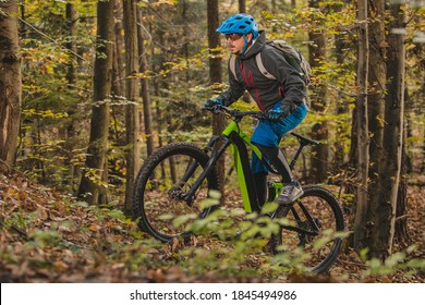 Biker riding uphill with a modern electric bicycle or mountain bike in autumn or winter setting in a forest. Modern e-cyclist in woods.