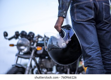 biker riding wear jeans with helmet and classic motorcycle blur background