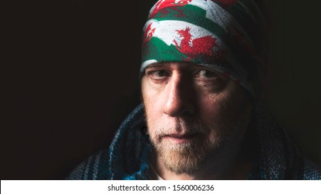 Biker in shadowy light with stubble beard and staring eyes wearing a buff on his head made from the national flag of Wales showing the red dragon.