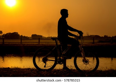 biker silhouette near the lake at sunset