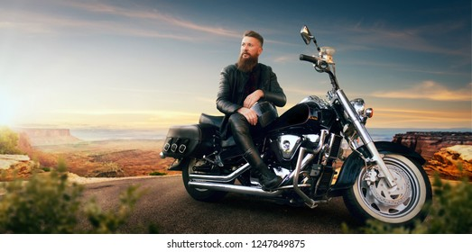 Biker sitting on his chopper and looks on sunset