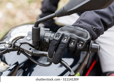 Biker sitting on motorcycle on an empty road, close-up view on hands on handlebars. Transportation concept.