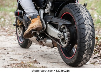Biker sitting on motorcycle on an empty road, close-up view on legs. Transportation concept.