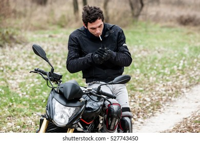 Biker sitting on motorcycle on an empty road, and smoking his cigarettes. Transportation concept.