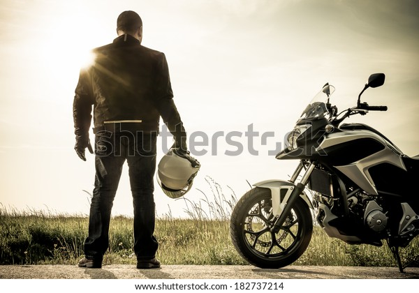 Biker standing with its motorbike on a misty sunset.