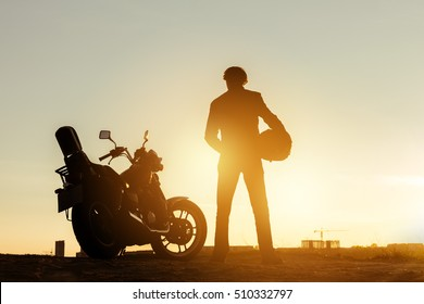 Biker stands near motorcycle at sunset time and holds helmet