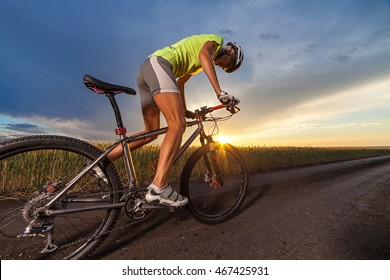Biker starting to ride on the rural road at the sunset against blue sky with clouds. Close up view.