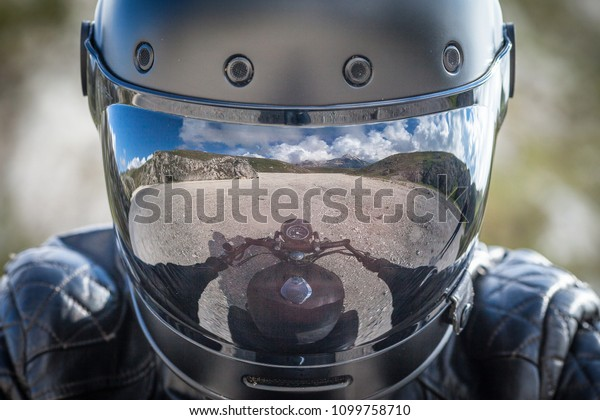 Le cycliste reste sur sa moto avec un paysage de montagne désolé reflété sur son viseur de casque