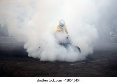 biker staying on bike on road with smoke of the tire, burn out in the moto show