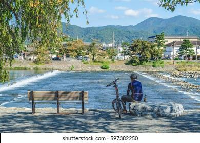 Biker stop and rest for breathing fresh air in Arashiyama Park Nakanoshima Area, Kyoto, Japan.
