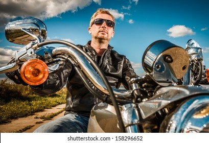 Biker in sunglasses and a leather jacket on a motorcycle