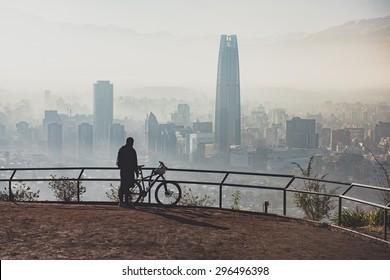 Biker at the top of the city. Santiago de Chile cityscape.