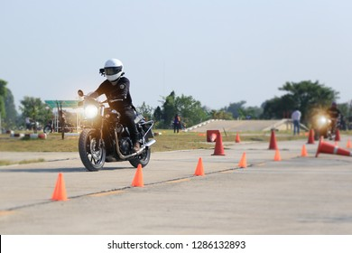 Biker training of riding safety course in diving school with traffic cone on street. Riding motorcycle in driving school.