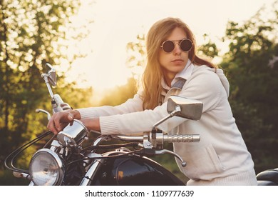 Biker wearing sunglasses and a jacket at wheel of a motorcycle. Guy with long hair. Sunny sunset.