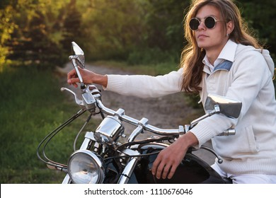 Biker wearing sunglasses and jacket at wheel of a motorcycle. Guy with long hair. Portrait on background of rural road. Stop on road trip.