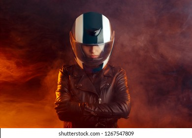 Biker Woman with Helmet and Leather Outfit Portrait. Cool competitive female motorcyclist wearing protective gear