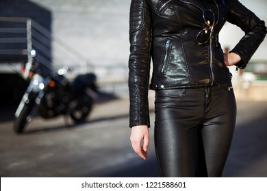 biker woman in leather jacket standing in front of motorbike. Street lifestyle