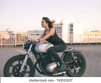 Biker woman ridding custom cafe racer motorcycle on empty city road at sunset