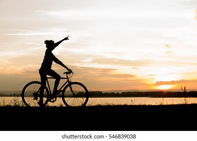 Biker-asian girl at the sunset on the meadow