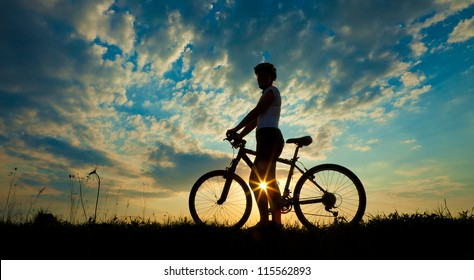 Biker-girl at the sunset on the meadow