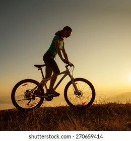 Biker-girl at the sunset on mountains