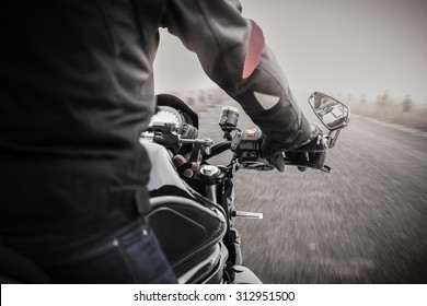 Bikers driving a motorcycle on misty asphalt road in black and white