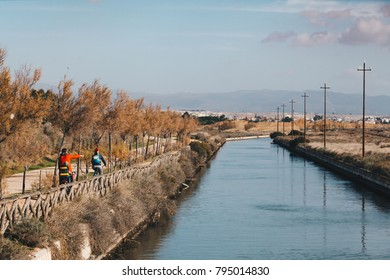 A bikers family runnig along the channel on the Molentargius Regional Park - Sardinia Italy.