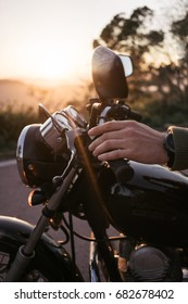 Biker's hand holding motorcycle handle on parking. Man sits on his old black motorbike on soft sunset ready to ride away