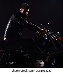 Bikers leisure concept. Macho, brutal biker in leather jacket riding motorcycle at night time, copy space. Man with beard, biker in leather jacket sitting on motor bike in darkness, black background.