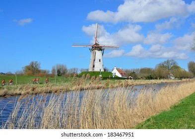 Bikers passing by an old windmill in Damme, near Bruges,  Flanders, Belgium