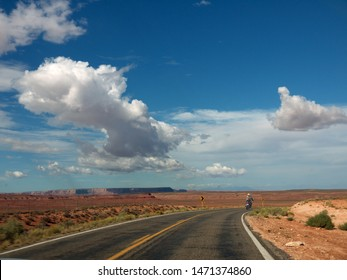 Bikers riding to Monument valley on lonely Arizona desert road on sunny day