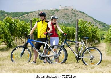 bikers, ruins of Devicky castle with vineyard, Czech Republic