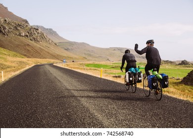 Bikers with saddle bags and helmets on tour around Iceland.Rear view of backpackers riding a bicycle in the mountains.Hikers with bikes.Sports and cycling,healthy lifestyle.Traveling on bikes