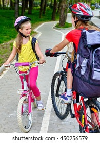 Bikes bicyclist girl. Girls wearing bicycle helmet and glass with rucksack ciclyng bicycle. Girls children cycling meet on white bike lane.