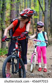 Bikes cycling family. Happy mother and daughter wearing helmet are cycling on bicycle into forest. Mother on bicycle looks back at her daughter.