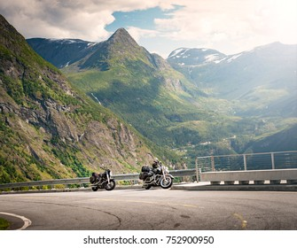 Bikes in mountains of Norway, Europe. Travel through scandinavia. Road in foreground, blue cloudy sky in background.